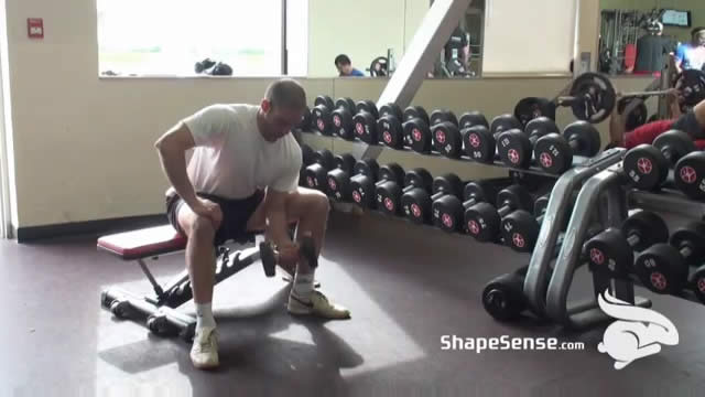 An image of a man performing the concentration curl exercise.