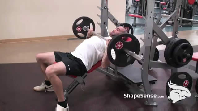 An image of a man performing the incline bench press exercise.