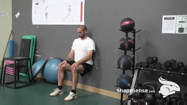 An image of a man performing the wall sit exercise.