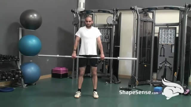 An image of a man performing the barbell shrug exercise.