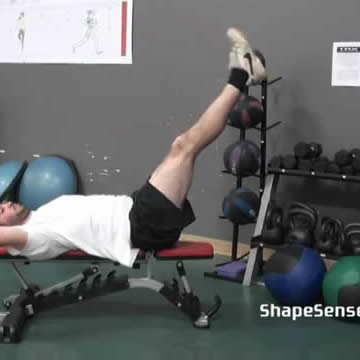 An image of a man performing the bench leg raise exercise.
