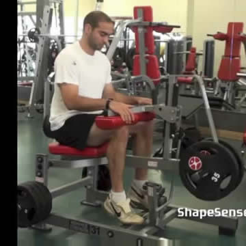 An image of a man performing the seated calf raise exercise.