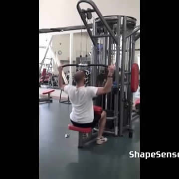 An image of a man performing the lat pull down exercise.