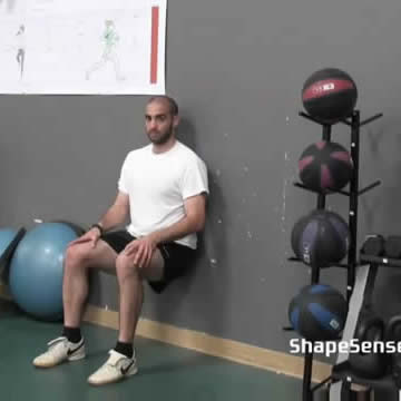 An image of a man performing the wall sit repetitions exercise.