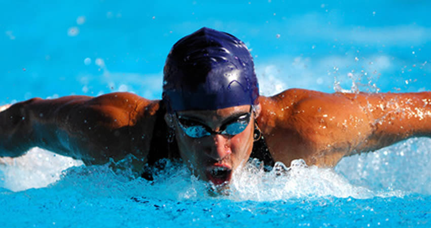 A fit man swimming butterfly stroke.