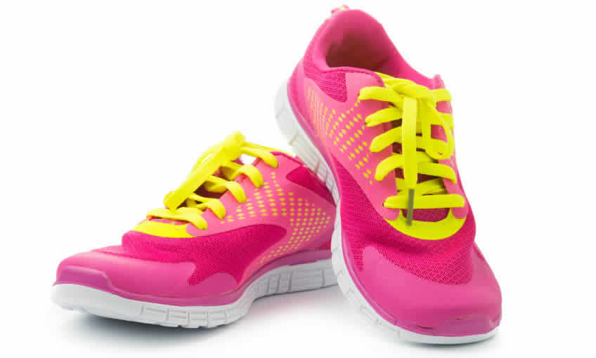 A pair of pink running shoes with yellow laces.