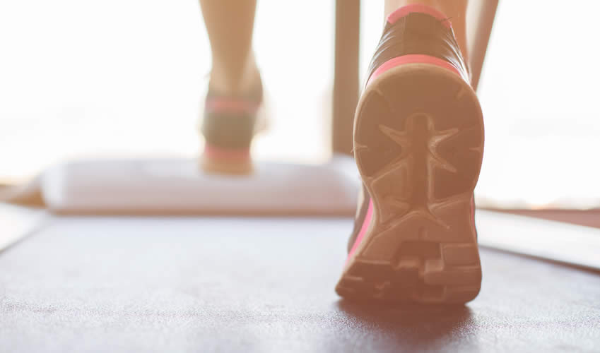 A pair of feet walking on a treadmill.