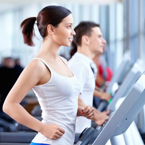 A woman walking on a treadmill in a fitness centre.
