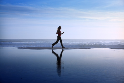 a woman jogging on the beach to improve cardiorespiratory fitness